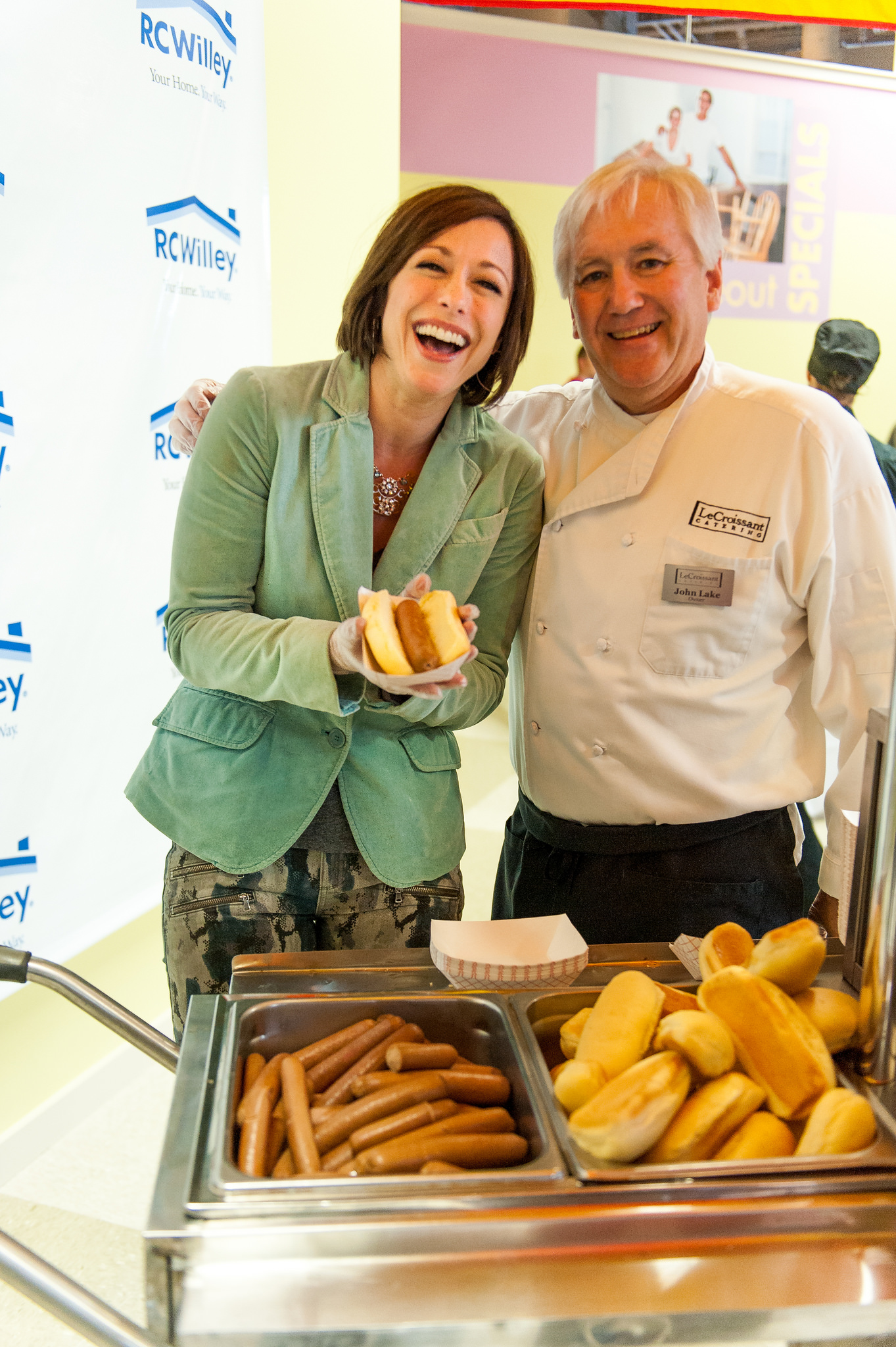 Lux Catering and Events co-owner, John Lake, with RC Willey spokeswoman Paige Davis enjoying our gourmet hot dogs.  Celebrate National Hot Dog Day with Gourmet Hot Dogs! Celebrate National Hot Dog Day with Gourmet Hot Dogs! 15357113974 49a95ee8f1 k