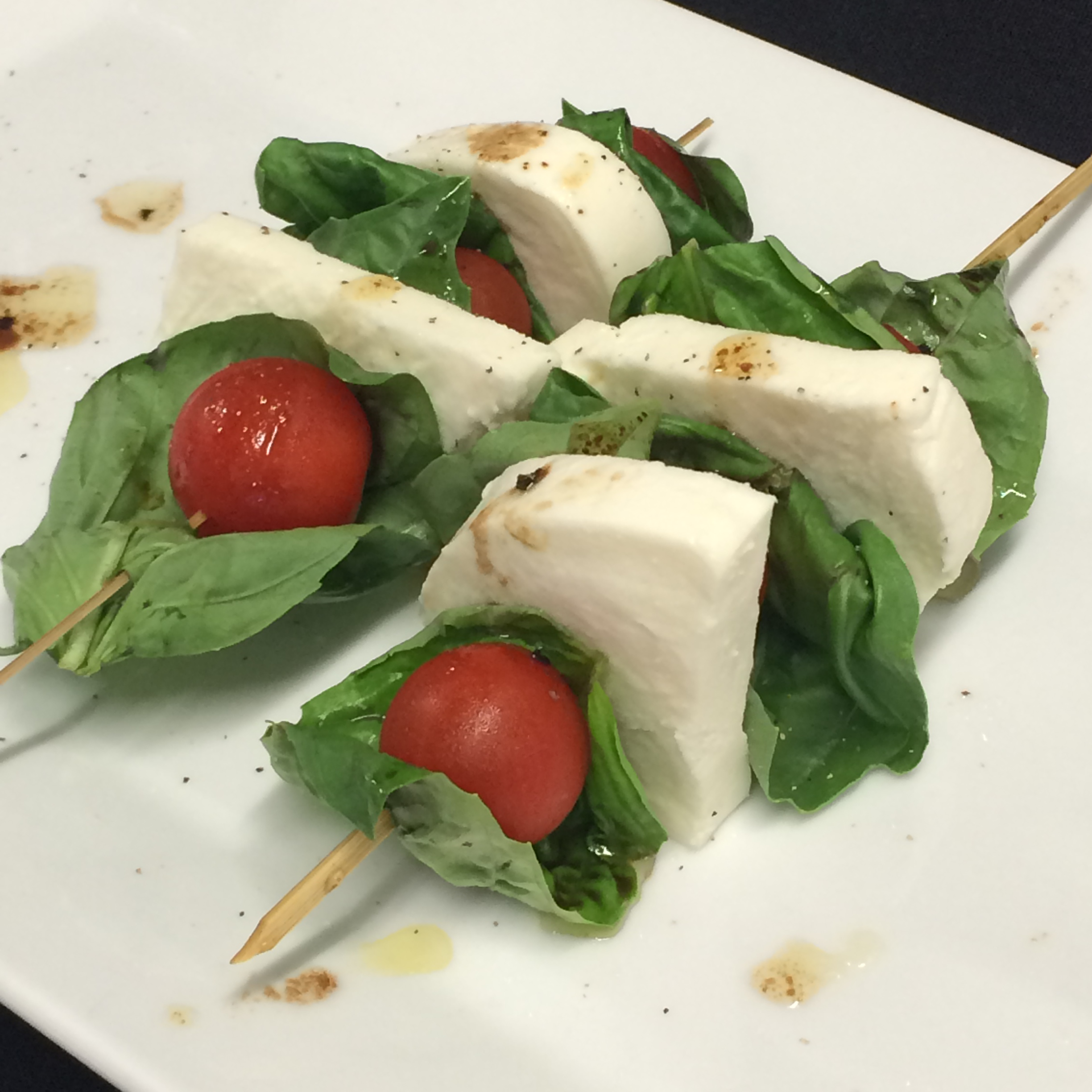 Caprese Salad Skewers with fresh, thickly-cut mozzarella and drizzled in balsamic vinegar and olive oil.