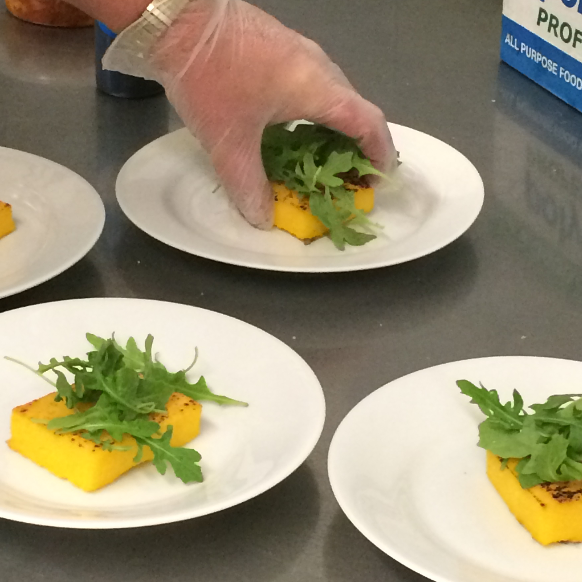 Grilled polenta cakes topped with arugula before being finished off with sun-dried tomatoes.  Gourmet Small Plates by LeCroissant Catering & Events Gourmet Small Plates by LeCroissant Catering & Events 2015 07 30 18